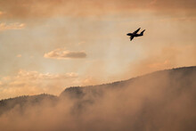 Silhouette Airplane Flying Over Smoke Emitting From Wildfire In Forest