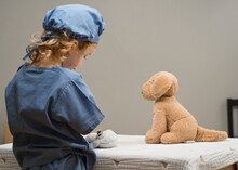 Young Child Wearing Medical PPE Attends To Plush Toy Dog Patient