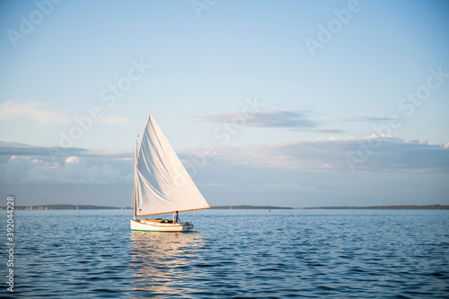 Photo Single one catboat sailboat sailing during golden hour summer sunset