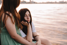 Thoughtful Lesbian Couple Sitting By River In City At Sunset