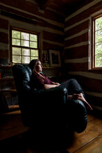 Woman Resting In Leather Recliner Chair In A Rustic Log Cabin Home.