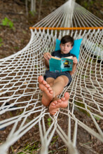 Young Boy Laying In A Woven Hammock Relaxing And Reading A Book.