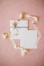 Wedding Invitation On Pink Backdrop.