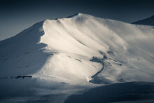 Mountain Detail Of A Snowy Peak Looking Along The Ridge. Split Toned, Low Key Image. Svalbard, A Norwegian Archipelago Between Mainland Norway And The North Pole