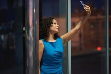 Night Portrait In The City Of A Young Woman With Smart Phone.