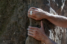 The Hands Of The Climber With A Tape Held To The Rock.