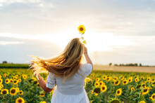 Young Attractive Blonde Woman Posing In Her Designer Dress In A Field Of Sunflowers