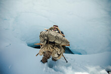 Mountaineer Approaches A Steep Hole, Access To Ice Cave.