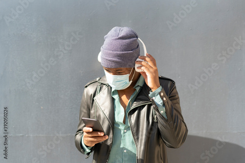young african man in the city listening to music from his smartphone