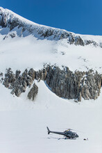 Helicopter Parked On Snow Covered Glacier Below Rocky Mountain Ridge.