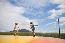 Boy And Girl Running On Trampoline, Outdoors In Rural Area.