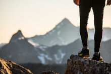 View Of Trail Runners Legs And Shoes Perched On A Mountain Summit.