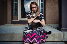 A Pre Teen Girl Holding Her Gray Cat On The Front Porch