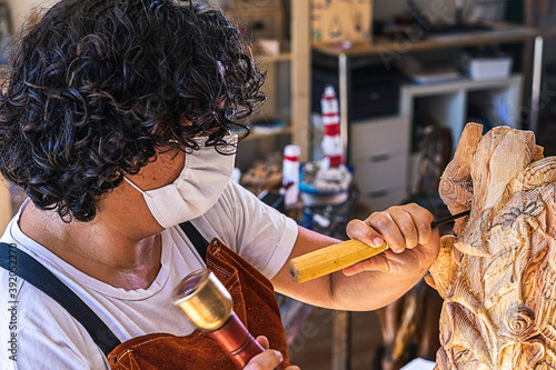 Craftswoman with mask carving wooden figure