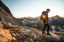 Backpacker Hikes Across Rocky Terrain On Mountain Pass.