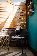 Two Year Old Standing On Chair While Peeking Through Fence