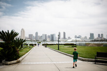 Young Boy Running With San Diego Skyline In Background