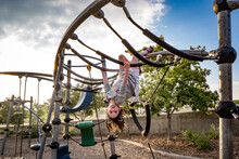Young Girl Hangs Upside Down At Playground