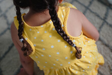 Little Girl With Braids In Yellow Dress From Behind