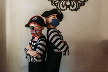 School Age Brothers Dressed As Pirates With Face Masks On At Home