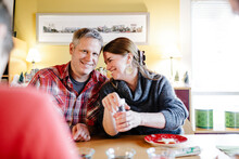 Lovely Smiling Couple Decorating During Holidays Time Sugar Cookies At Home