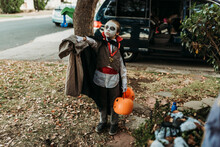 Elementary Age Boy Holding Out Bag Of Candy On Halloween
