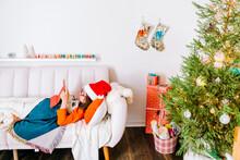 Kid Wearing Santa Hat Lying In...