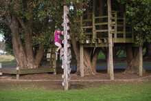 Young Girl Climbing On Wooden Playground Equipment At The Park