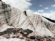 Mountaineer Climbing Up Ice Face Next To Running Melt-water River