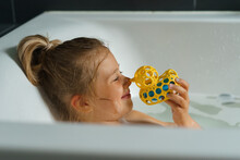 Portrait Of A Smiling Young Girl In Bath With A Rubber Duck.