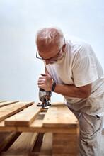 An Old Man Cutting Wood With A Jigsaw