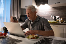 Elderly Male Transferring Money To Online Shop