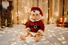 A Baby Girl Sits Looking At The Camera Dressed As A Santa Claus.