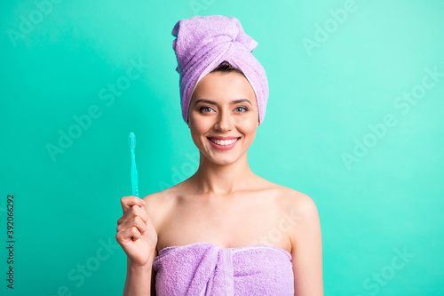Photo of charming young girl hold toothbrush beaming smile wear purple towel turban isolated turquoise color background