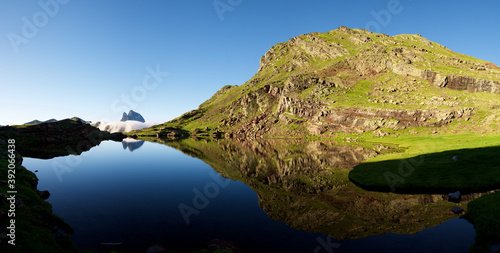 Ossau Peak reflected in Anayet lake in Tena Valley, Huesca province in Aragon, Pyrenees in Spain.