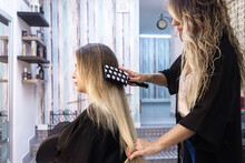 Hairdresser Combing Client Wit...