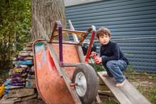 A Small Barefoot Boy Paints An...