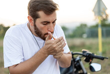 Fashionable Young Man Sitting And Smoking On A Classic Motorbike In Sunset.