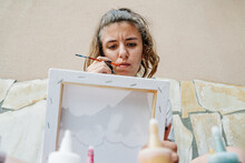 White Girl Sucking A Painting Brush While Thinking Of How Continue Her Picture. Horizontal Photo