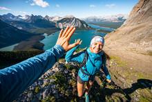 Hikers High Fiving Above Kananaskis Lake On Sarrail Ridge Summit