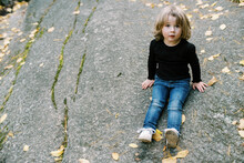 Cute Little Toddler Girl Sitting On A Slanted Rock