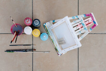 Painting Bottles, Brushes, Easel And Picture On The Floor Of A Terrace. Overhead Horizontal Photo