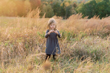 Five Year Old Girl Dispersing The Seed Of Dried Wild Flowers