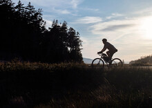 Cyclist Rides Bike Along Road In Acadia National Park, Maine