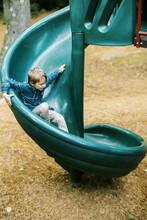 Little Boy Sliding Down A Twis...