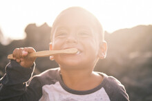 Portrait Of Kid Brushing Teeth With Bamboo Toothbrush