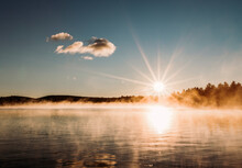 Rising Sun Star Over Peaceful Misty And Foggy Lake In Maine Woods