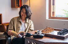 Woman Reading Book Next To Chess Table At Tea Lodge In Sri Lanka