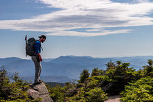 Man Standing At Top Of Mountain Looking Down In The White Mountains.