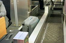 Checked In Bags And Luggage On Transport Belt Of Airport Check-in Desk